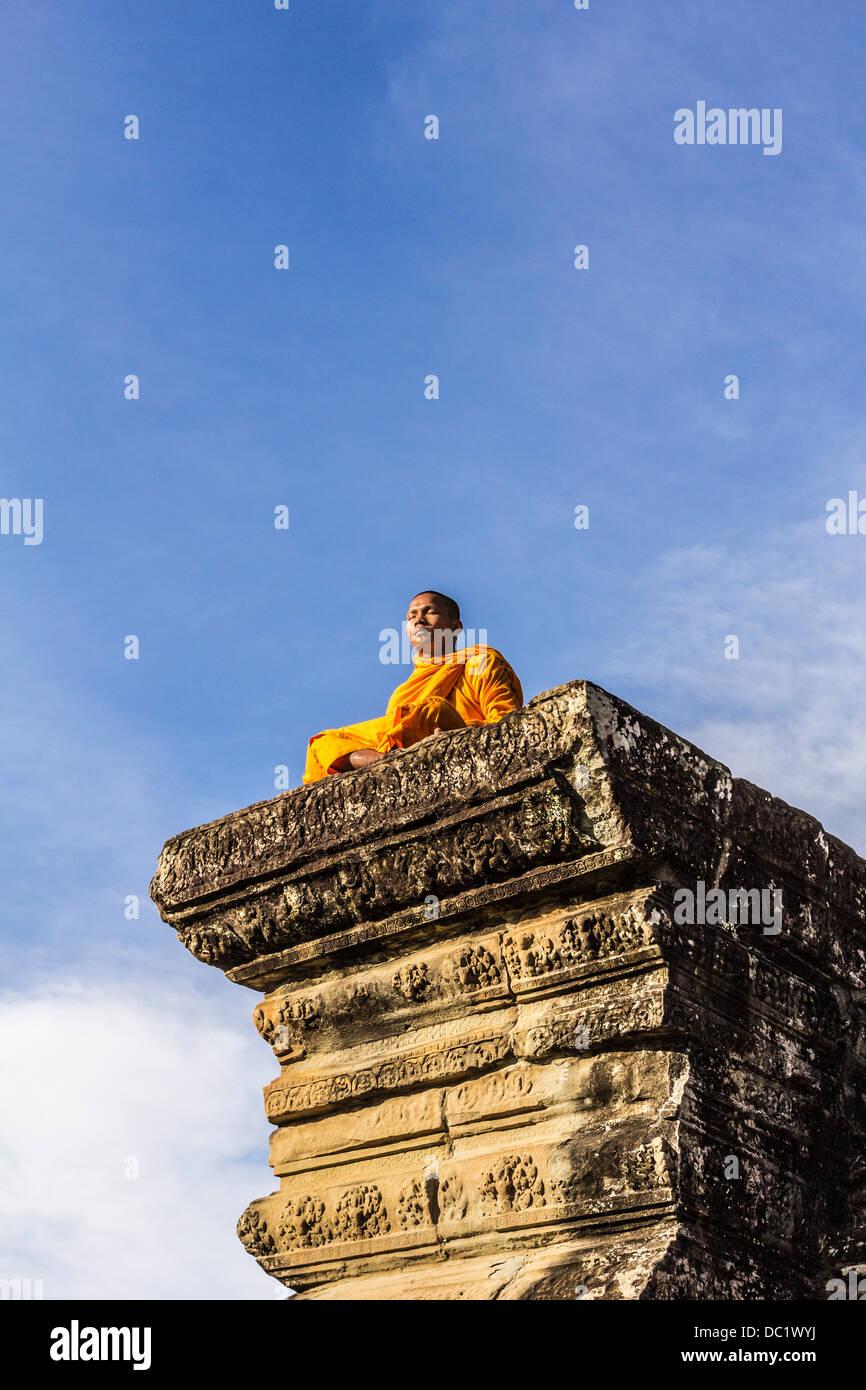 Junge buddhistische Mönch sitzt außerhalb der Tempel in Angkor Wat, Siem Reap, Kambodscha Stockbild