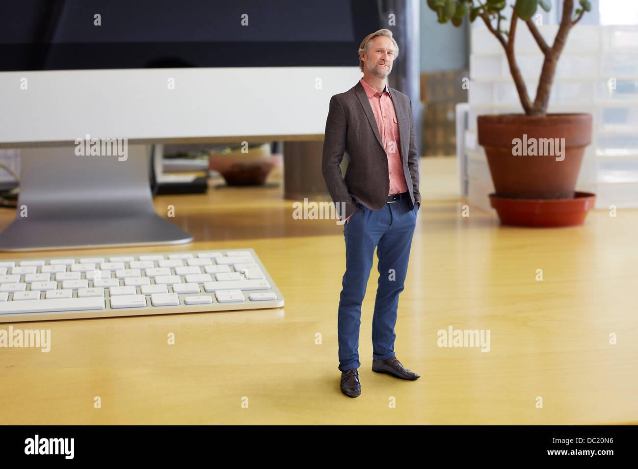 Reife Geschäftsmann auf übergroße Schreibtisch stehend Stockbild