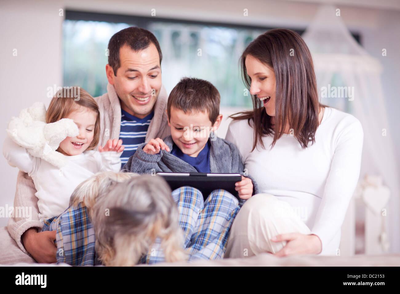 Eltern, zwei Kinder und Hund Blick auf digital-Tablette Stockbild