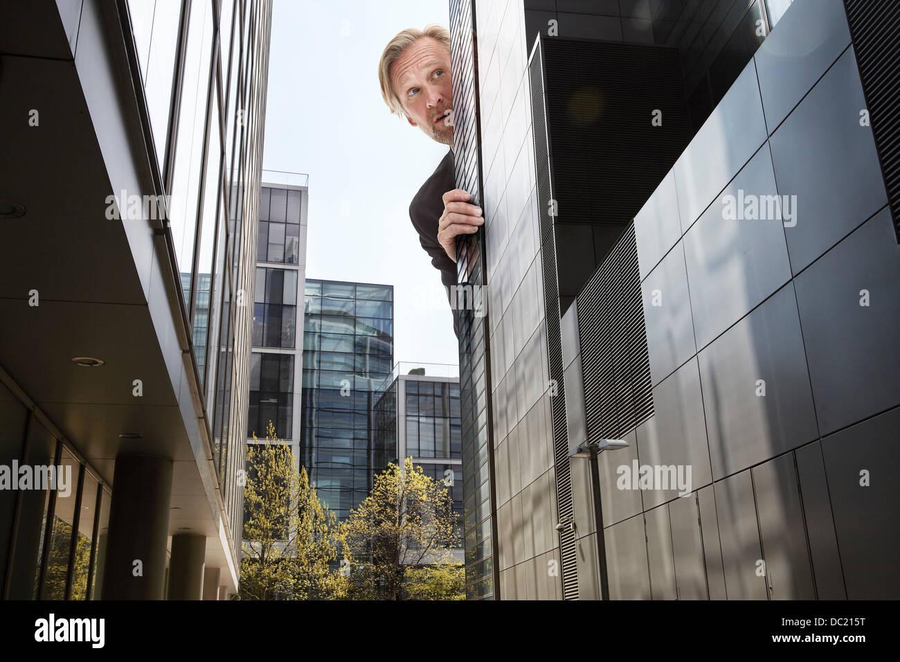 Übergroße Geschäftsmann peering von Wolkenkratzern, niedrigen Winkel Ansicht hinten Stockbild