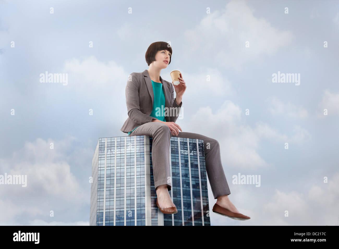 Übergroße Geschäftsfrau sitzen auf Wolkenkratzer, niedrigen Winkel Ansicht Stockbild