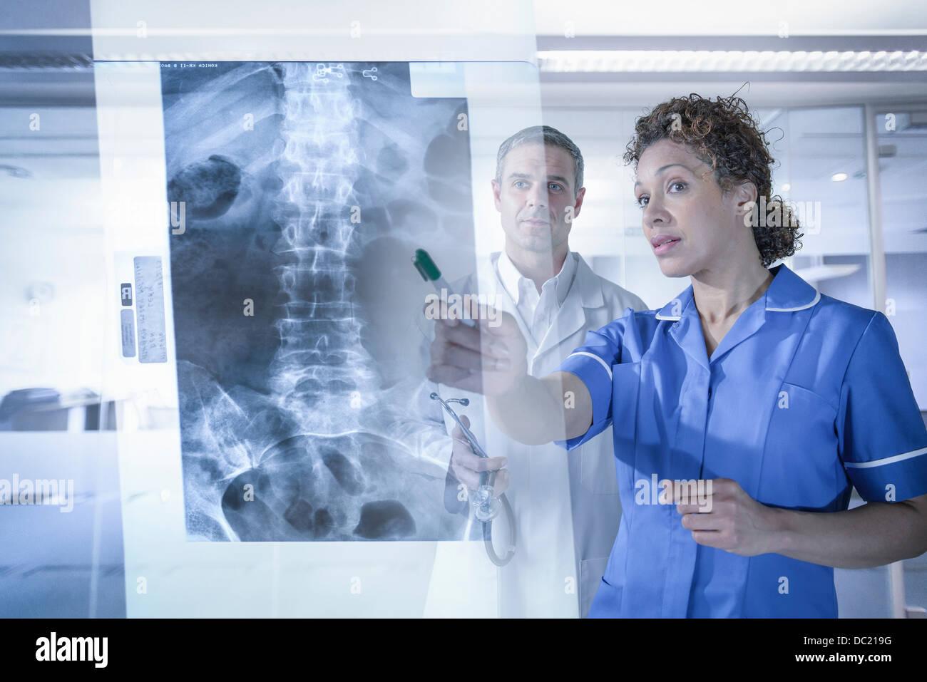 Arzt und Krankenschwester in der Xray Ergebnisse auf dem Bildschirm angezeigt Stockbild