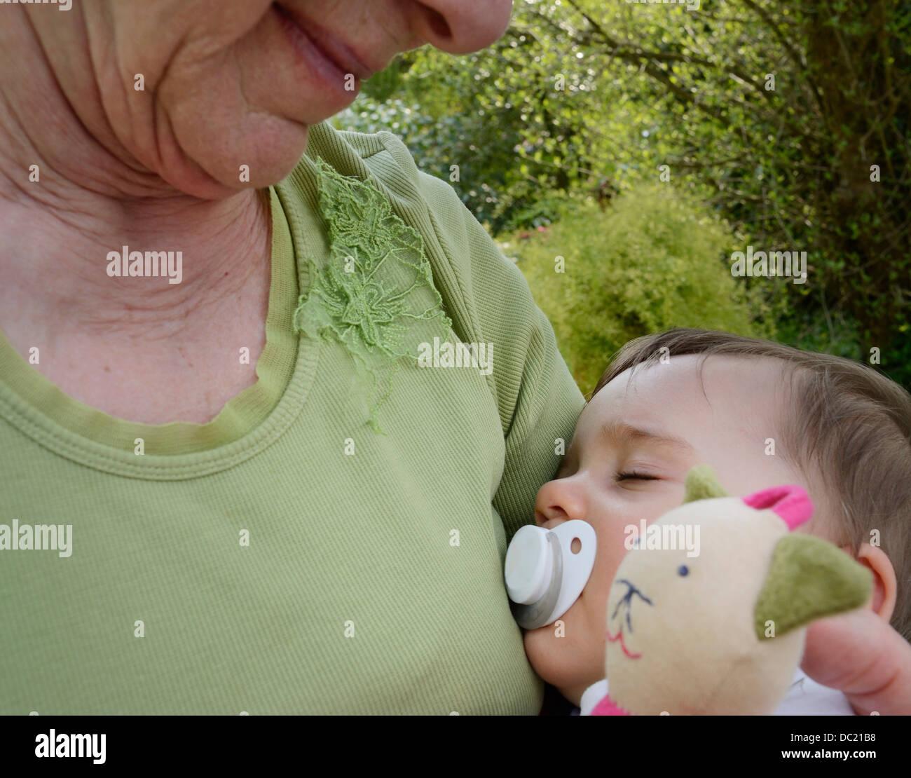 Ältere Frau mit schlafenden Enkelin, Nahaufnahme Stockbild