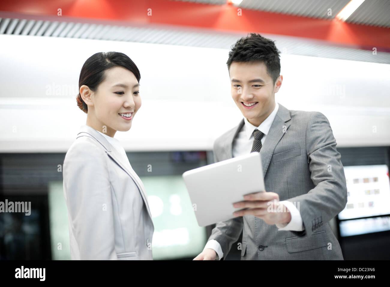 Junge chinesische Geschäftspartner mit digital-Tablette auf u-Bahn-Plattform Stockfoto