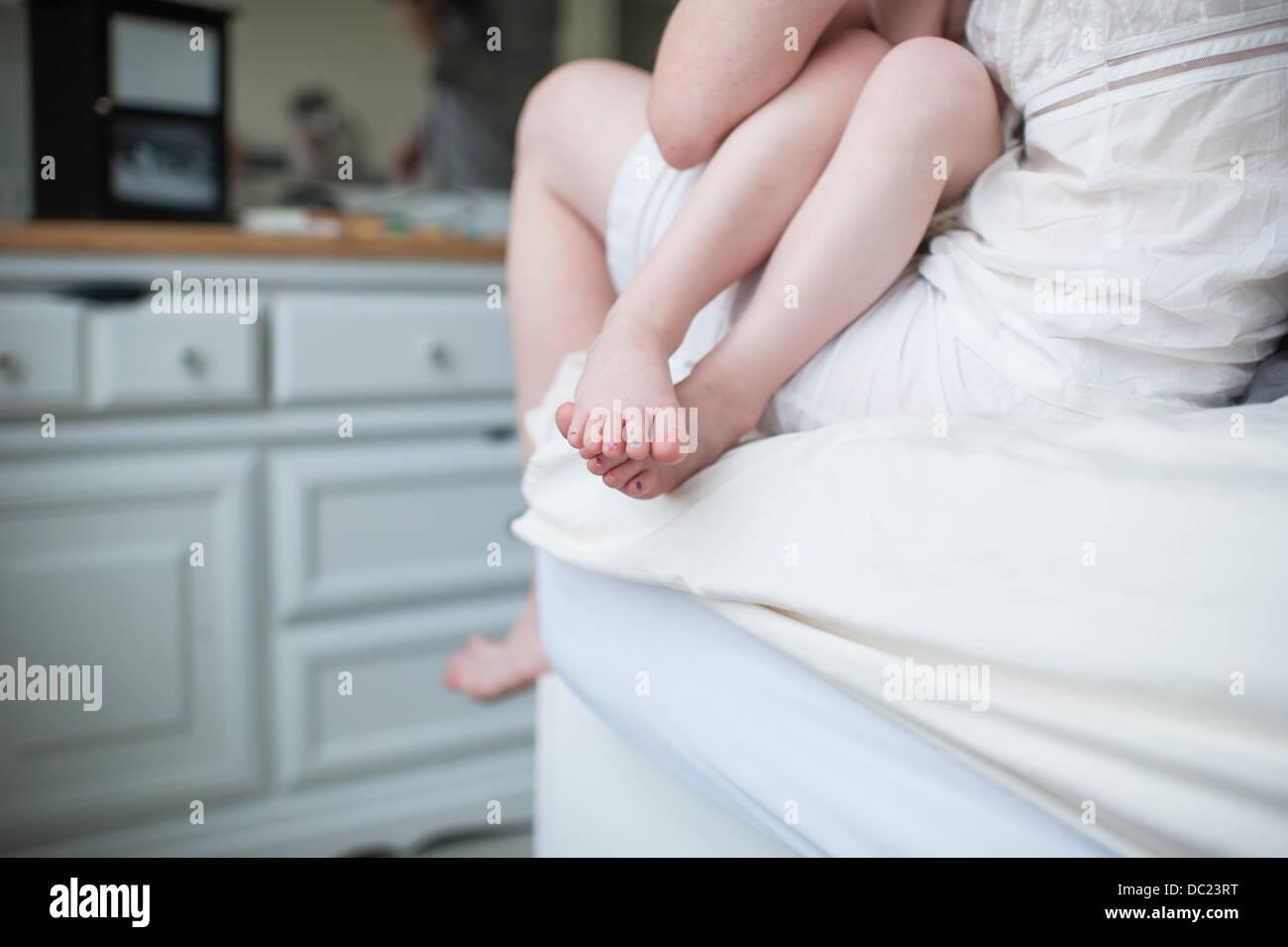 Tochter sitzen auf Mutters Knie, zugeschnittene Zusammensetzung der nackten Beine und Füße Stockbild