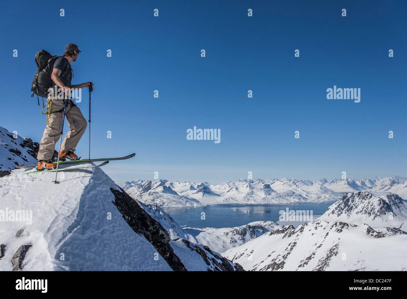Mann mit Skiern am Gipfel des Berges in Ostgrönland Stockbild