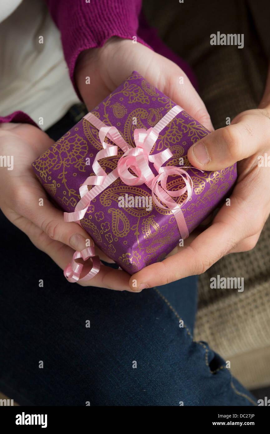Zwei Personen halten Geschenkbox mit rosa Schleife Stockbild