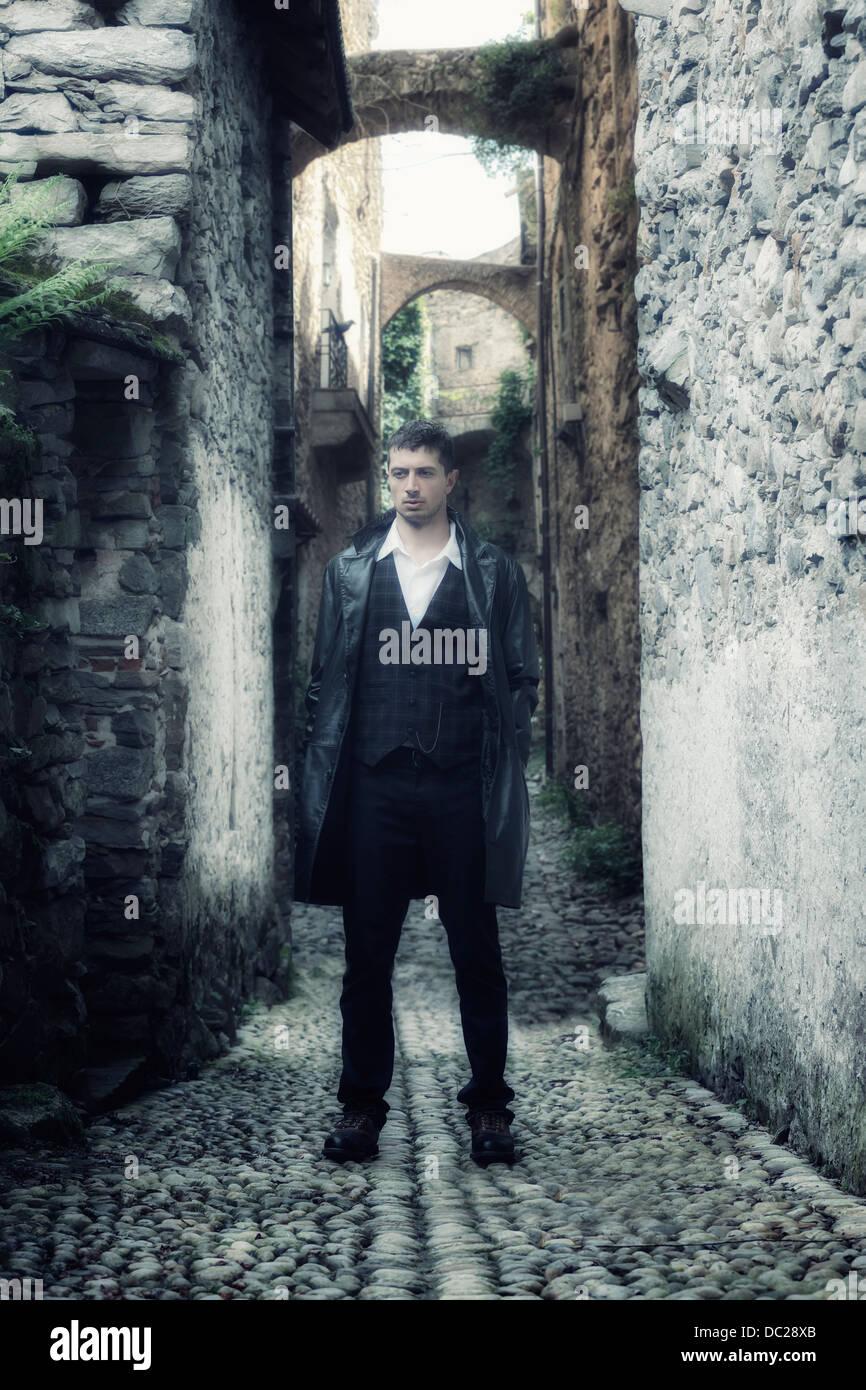 ein Mann in einer schwarzen Lederjacke steht in einer alten, schmalen Gasse Stockbild