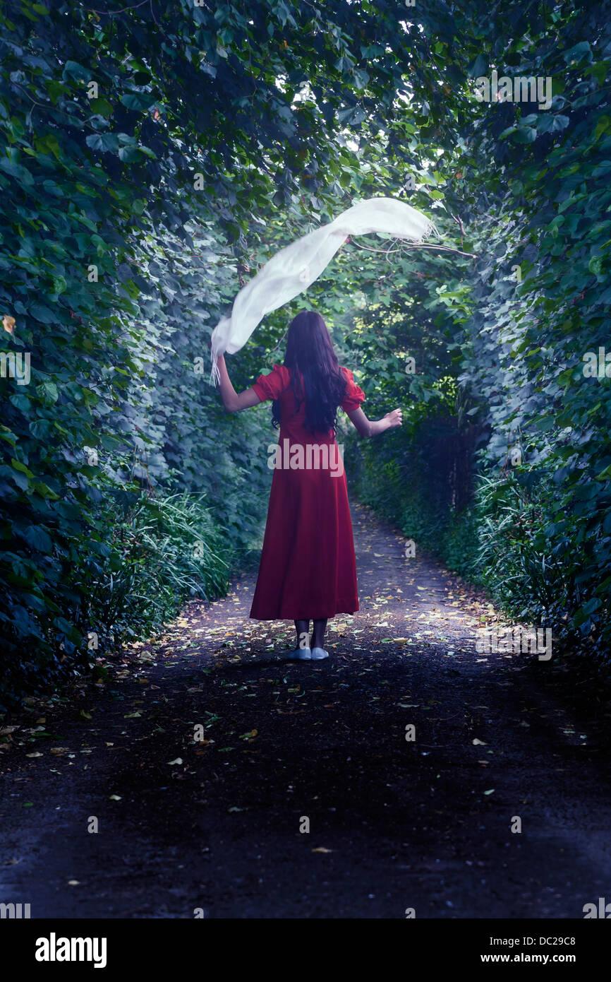 eine Frau in einem roten Kleid ist Fuß durch den Wald mit einem weißen Schal Stockbild