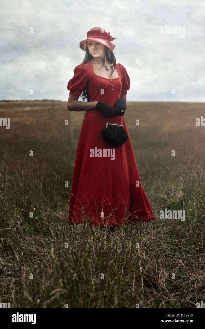 eine Frau in einem roten Kleid steht auf einem Feld Stockbild
