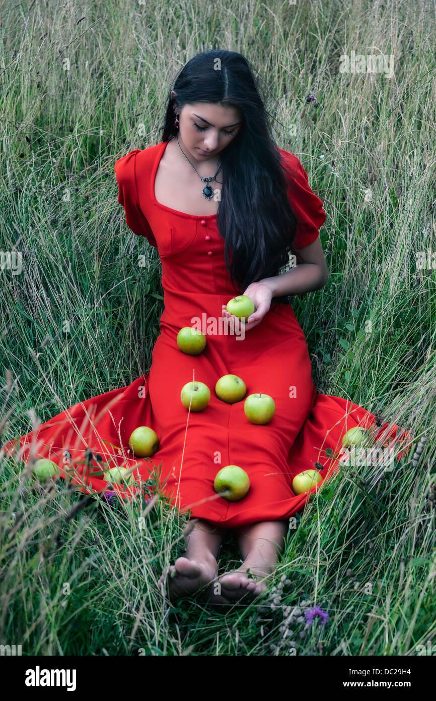 eine Frau in einem roten Kleid sitzt auf einem Feld mit grünen Äpfeln an ihrem Kleid Stockbild