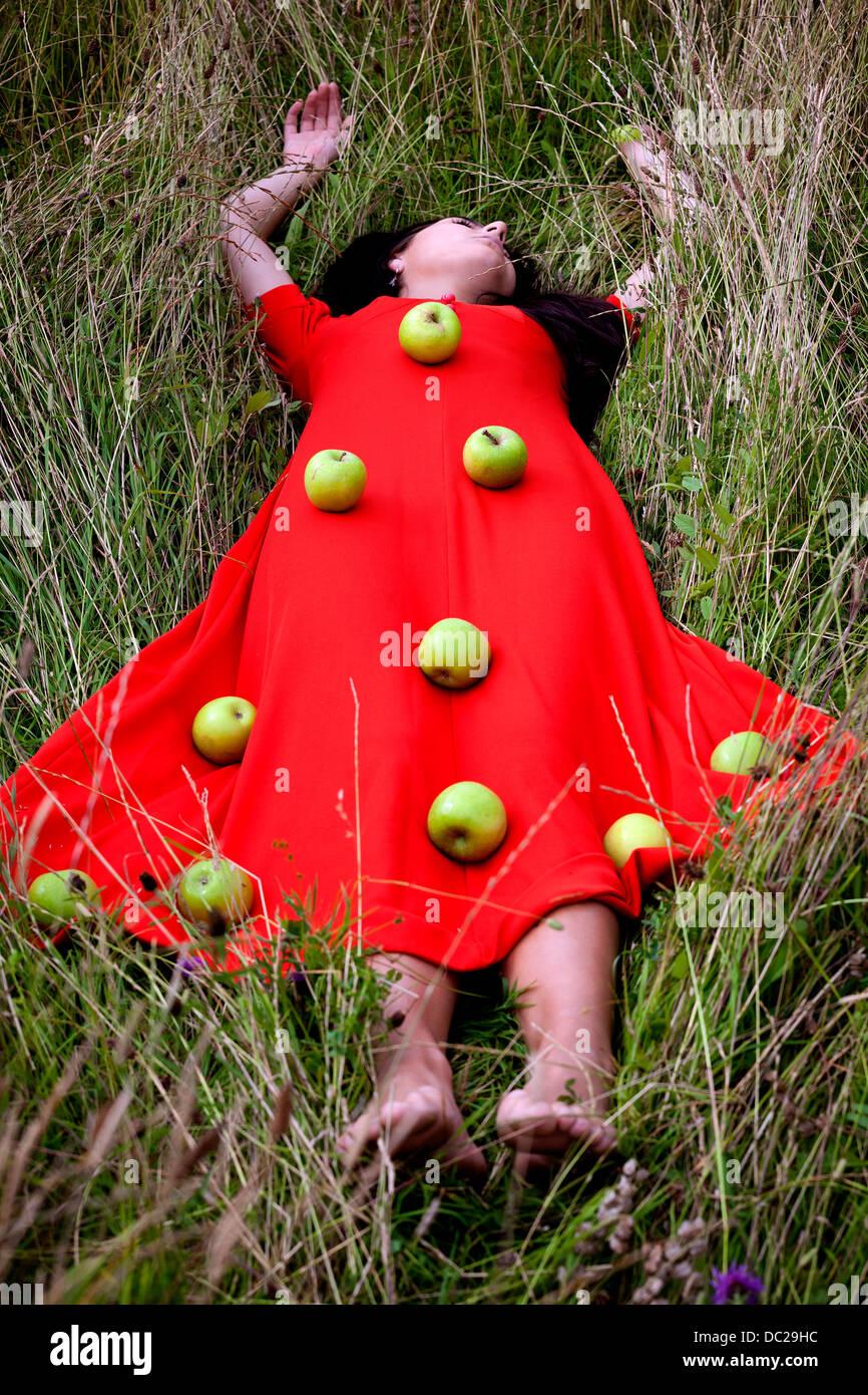 eine Frau in einem roten Kleid, liegt auf der Wiese mit grünen Äpfeln an ihrem Kleid Stockbild