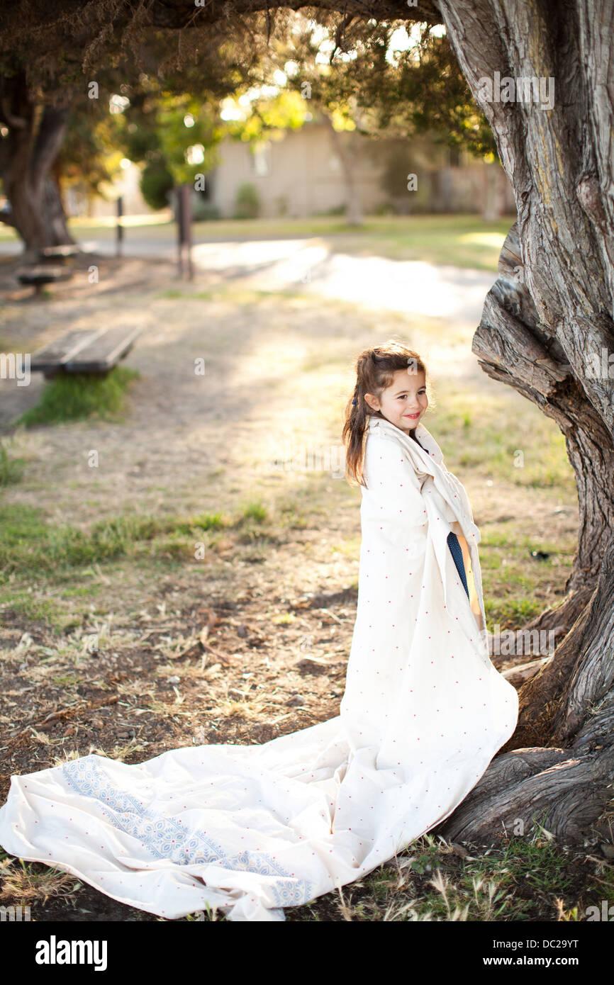 Porträt eines Mädchens in Blatt unter Baum gewickelt Stockbild