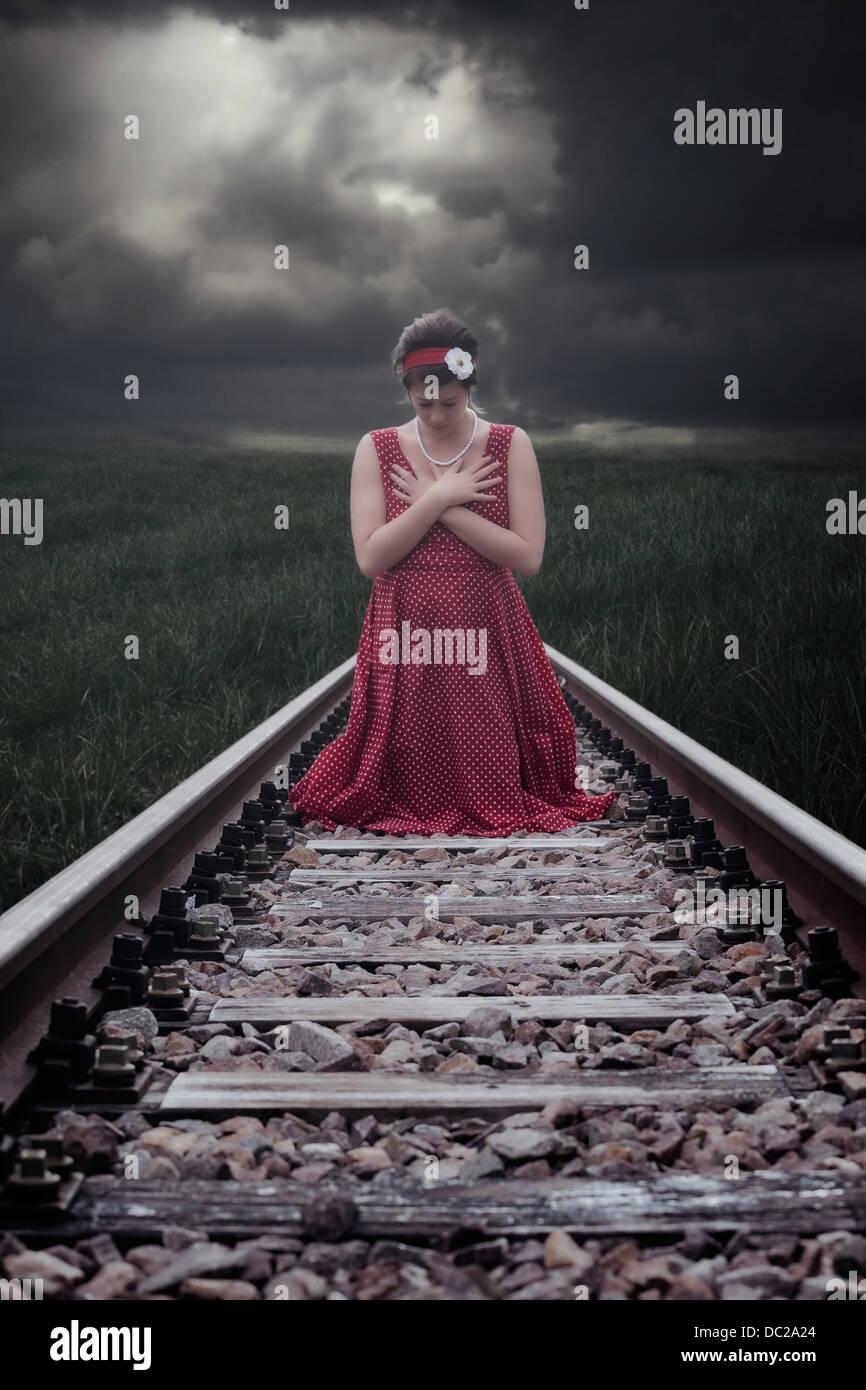 eine Mädchen in einem roten Kleid sitzt auf Bahngleise Stockbild