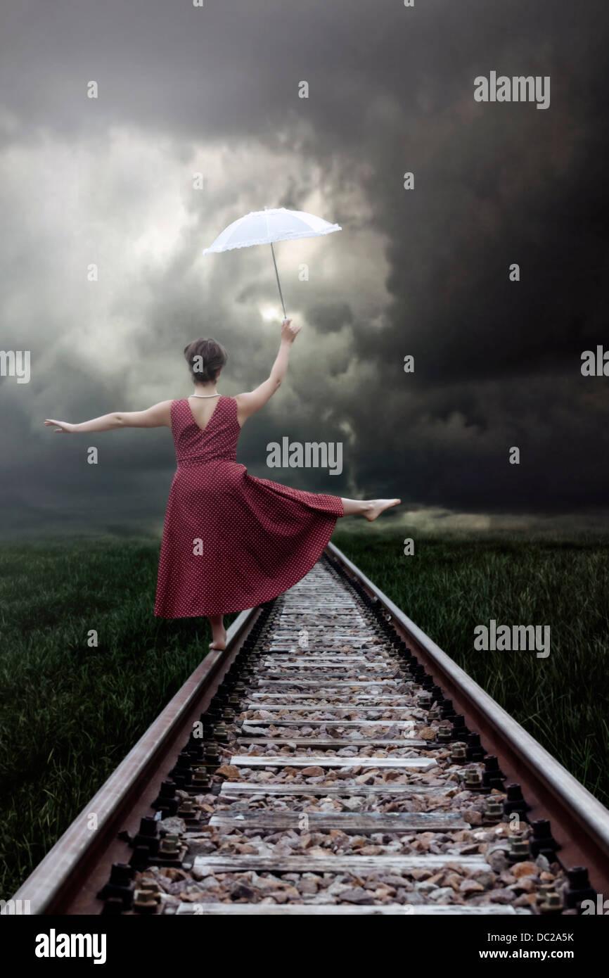 eine Mädchen in einem roten Kleid balanciert auf Schienen mit einem weißen Sonnenschirm Stockbild