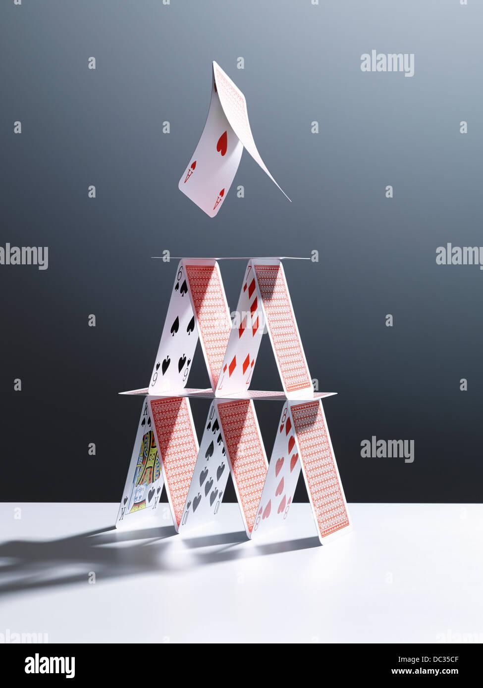 Karten über Kartenhaus springen Stockbild