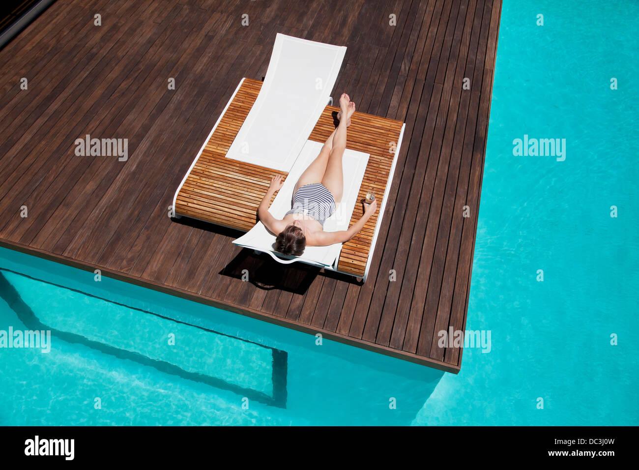 Frau Sonnenbaden am Pool Stockbild