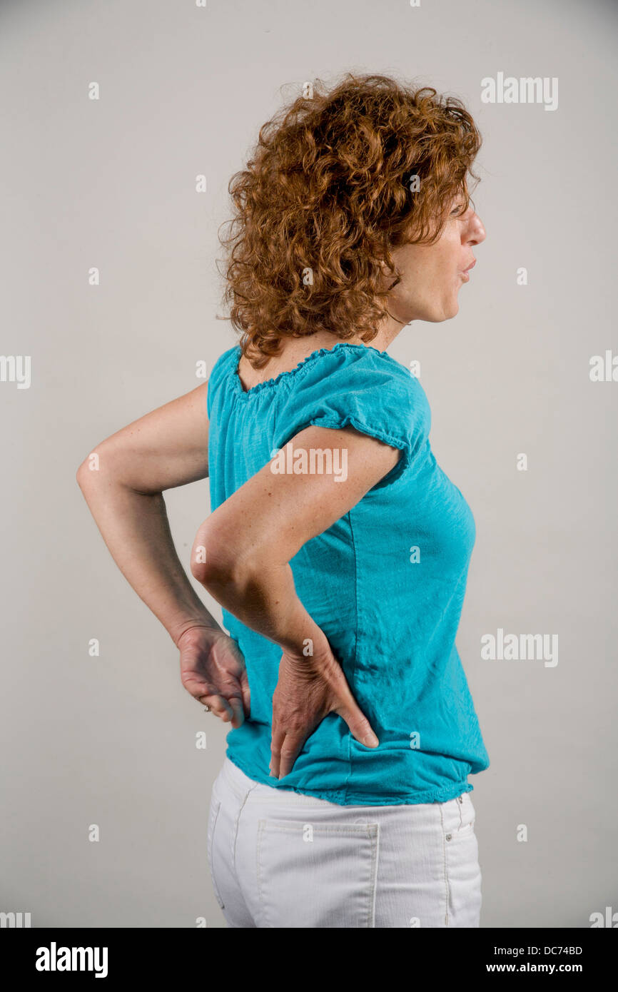 Eine 50 Jahre alte rote kurzhaarige Frau zeigt Schmerzen im unteren Rücken. Stockbild