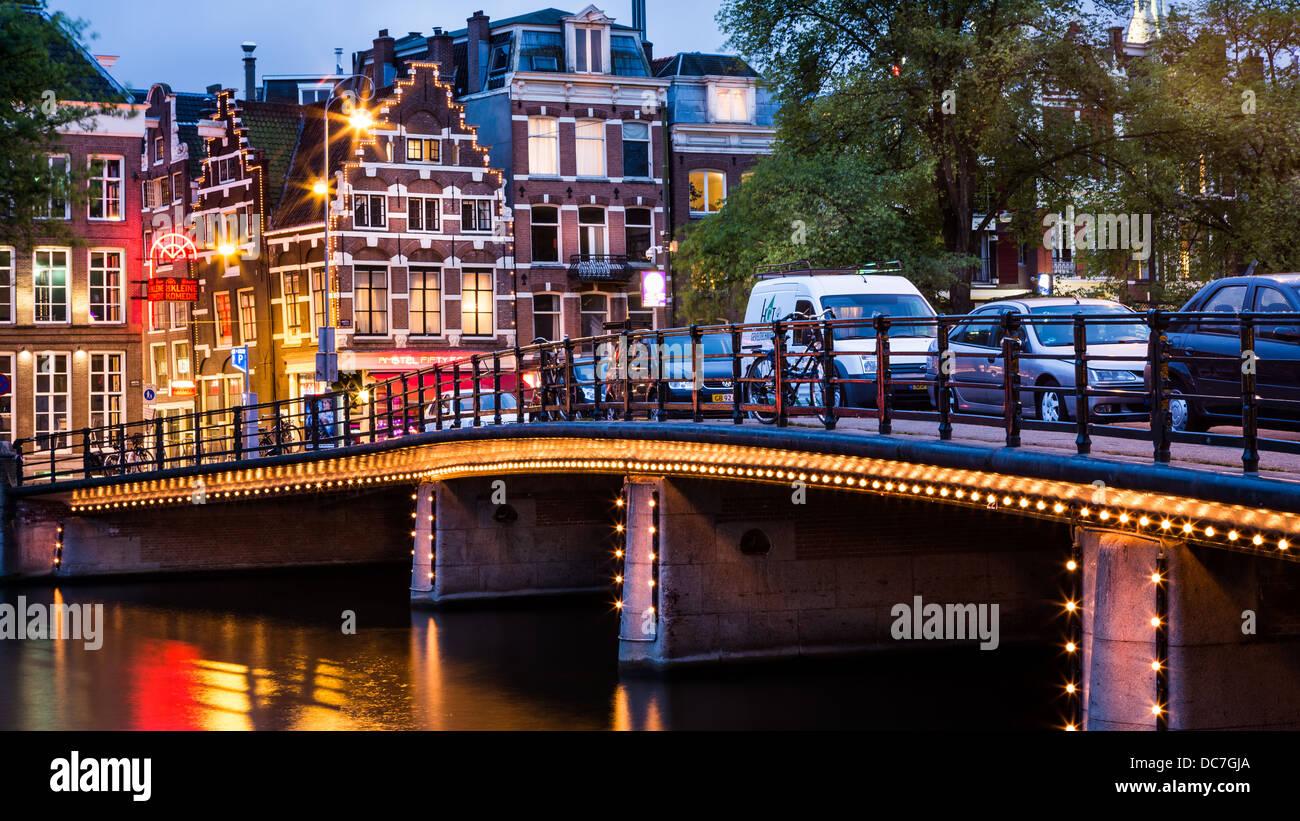 Halvemaans Brücke aus Amsterdam, beleuchtet, mit typischen holländischen Häusern im Hintergrund Stockbild