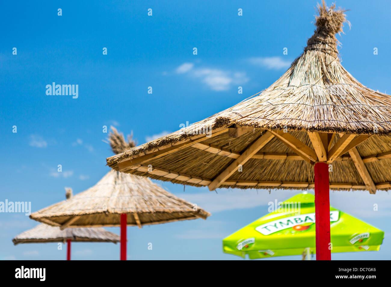 Reihe von Stroh Sonnenschirme Stockbild