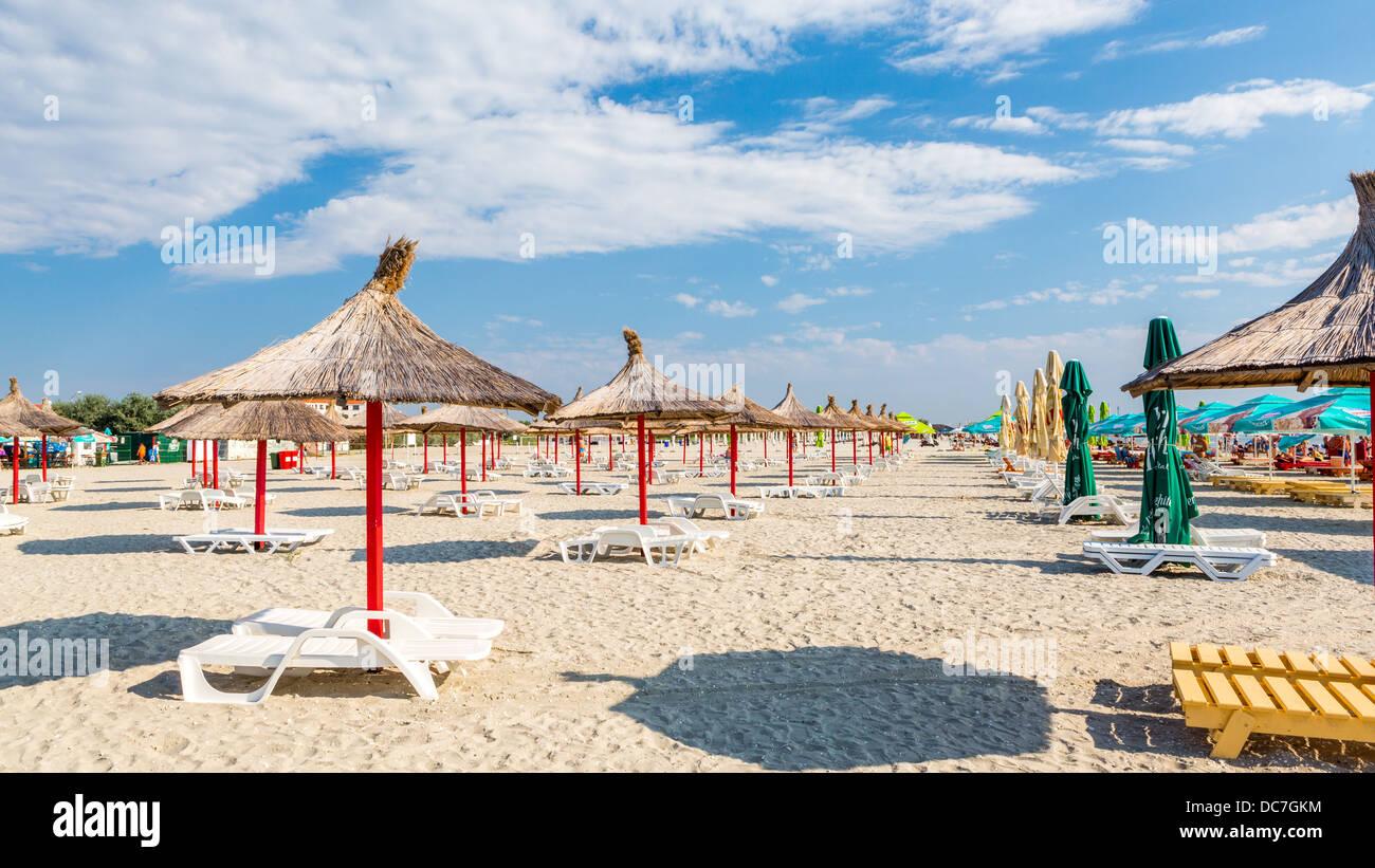Zeile und Stroh Sonnenschirmen und liegen am Sandstrand Stockbild