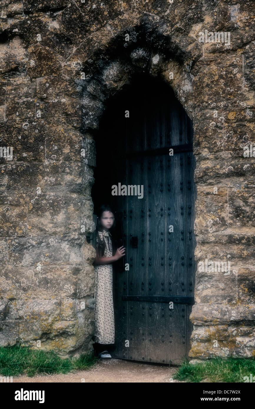 eine Mädchen sucht aus einer alten Tür Stockbild