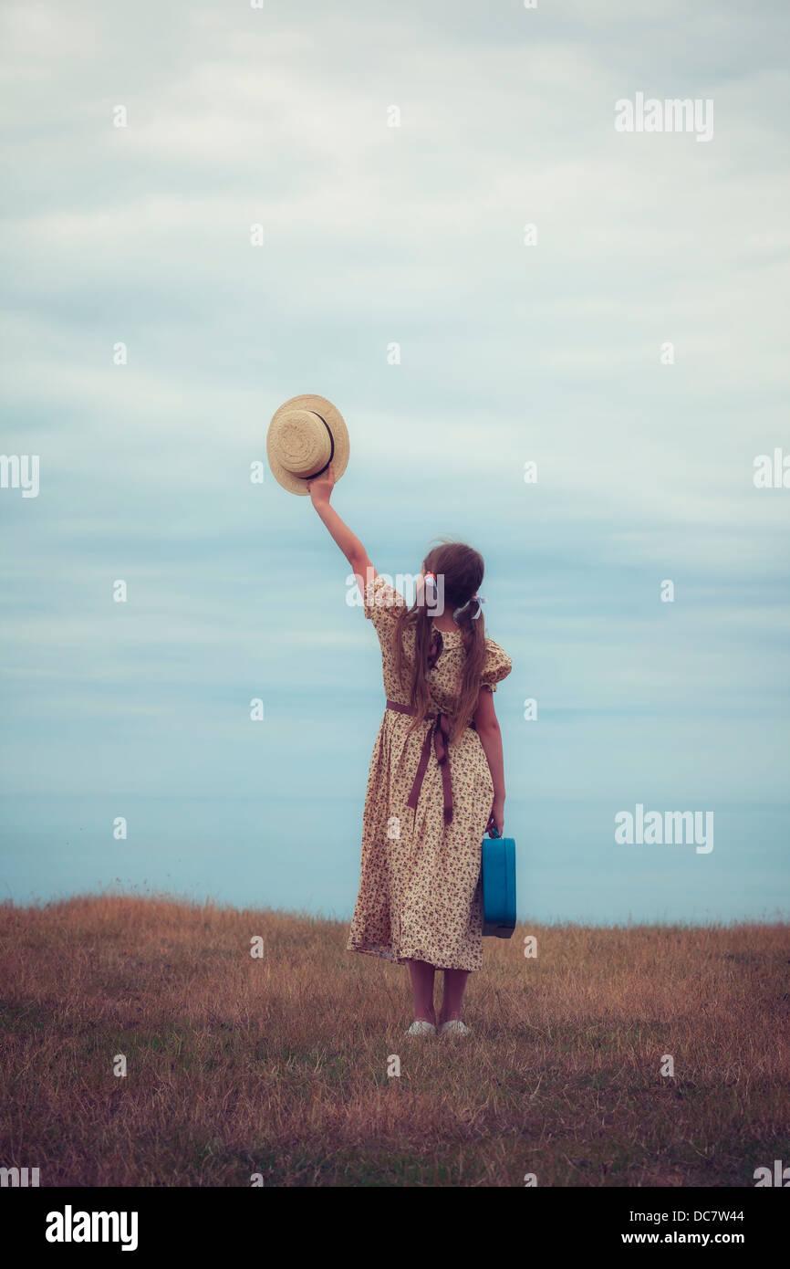 ein Mädchen in ein Vintage-Kleid mit Koffer hält einen Hut Stockbild