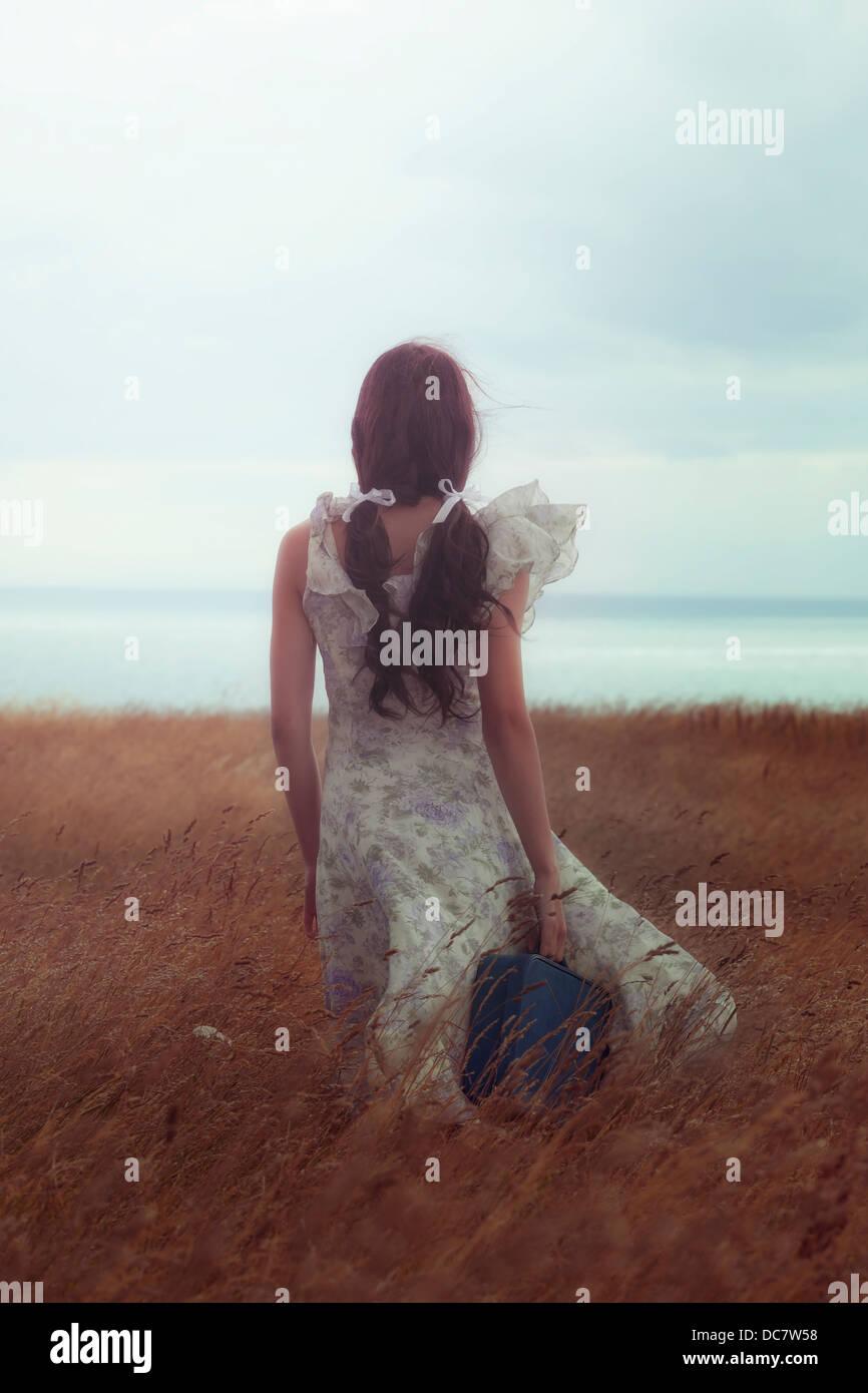 ein Mädchen in einem geblümten Kleid auf einem Feld mit einem Koffer Stockbild