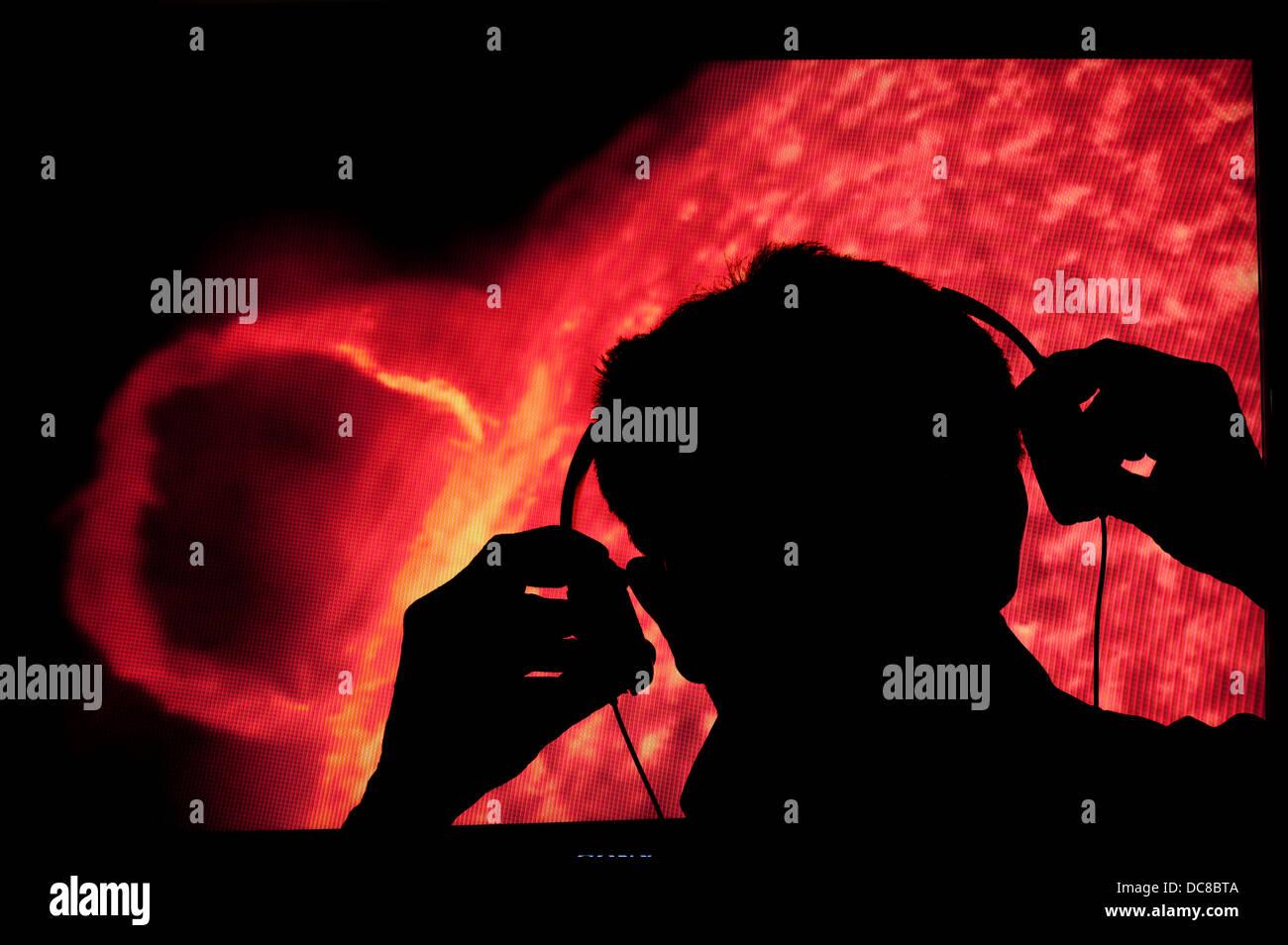 Mann-Wissenschaftler mit Kopfhörern Überwachung Klänge aus Sonne Stockbild