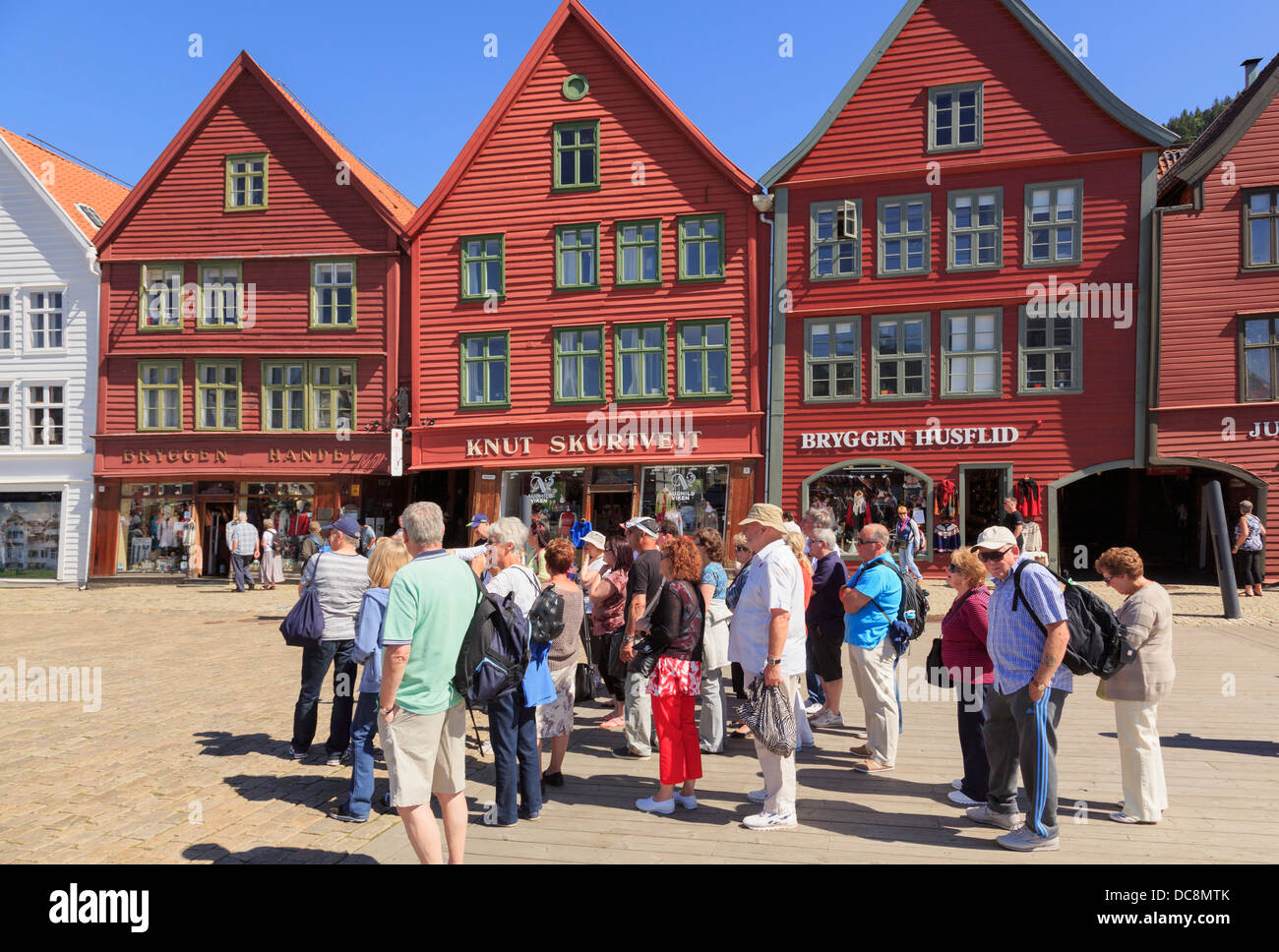 Touristen-Gruppe durch 14. Jahrhundert mittelalterliche Hansestadt Holzhäuser am Wasser im alten Hafen Stadtteil Stockbild