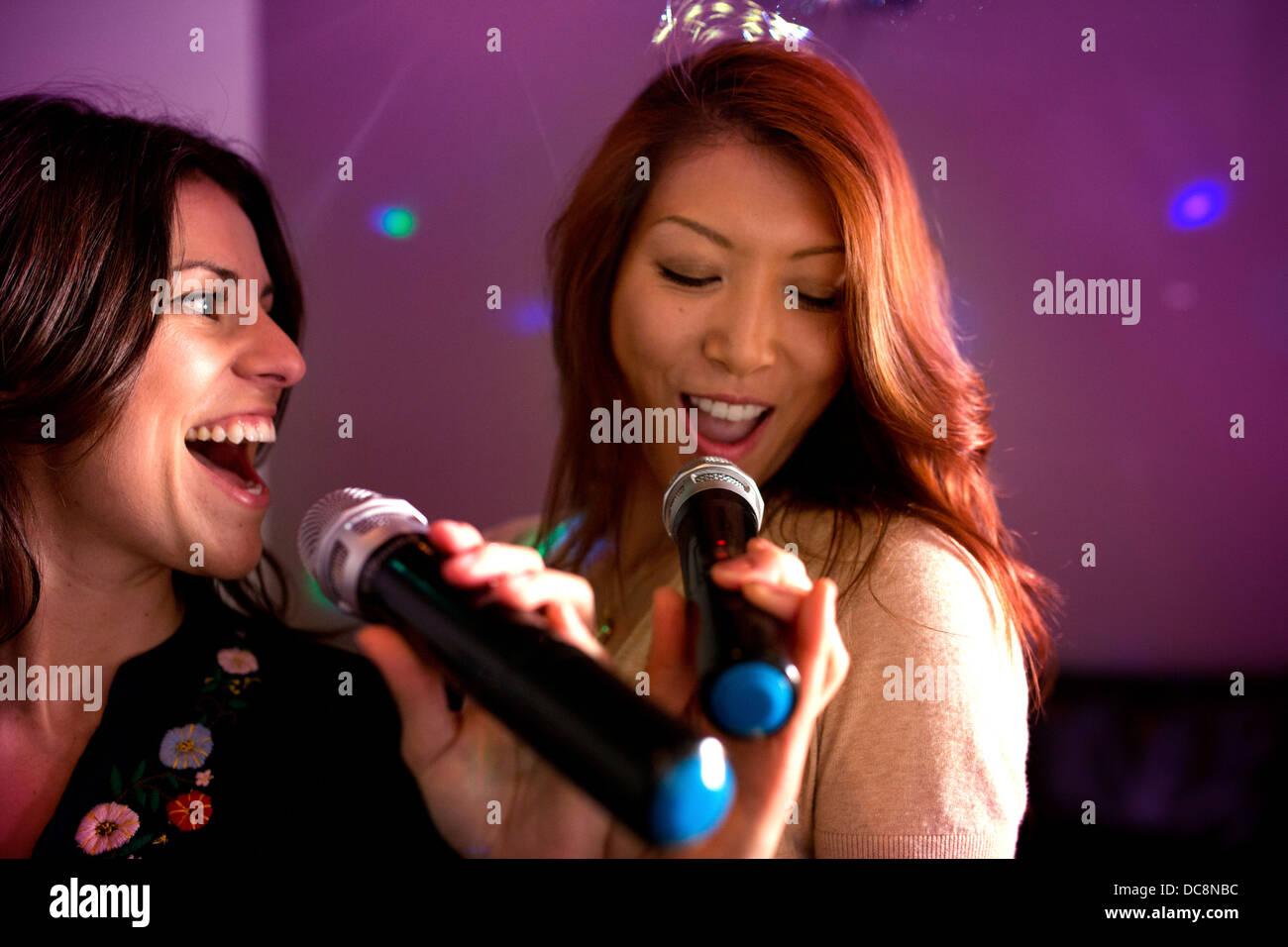 Zwei Frauen singen Karaoke. Stockbild