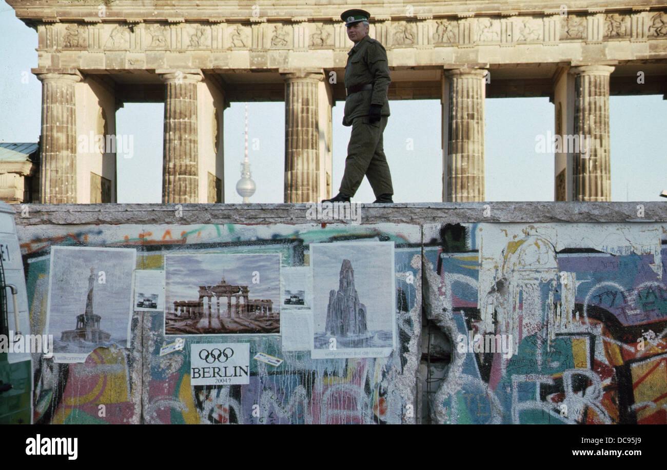 Öffnung der Berliner Mauer - DDR NVA Grenzschutz Fuß oben auf der Mauer auf der westlichen Seite der Sperranlage Stockbild