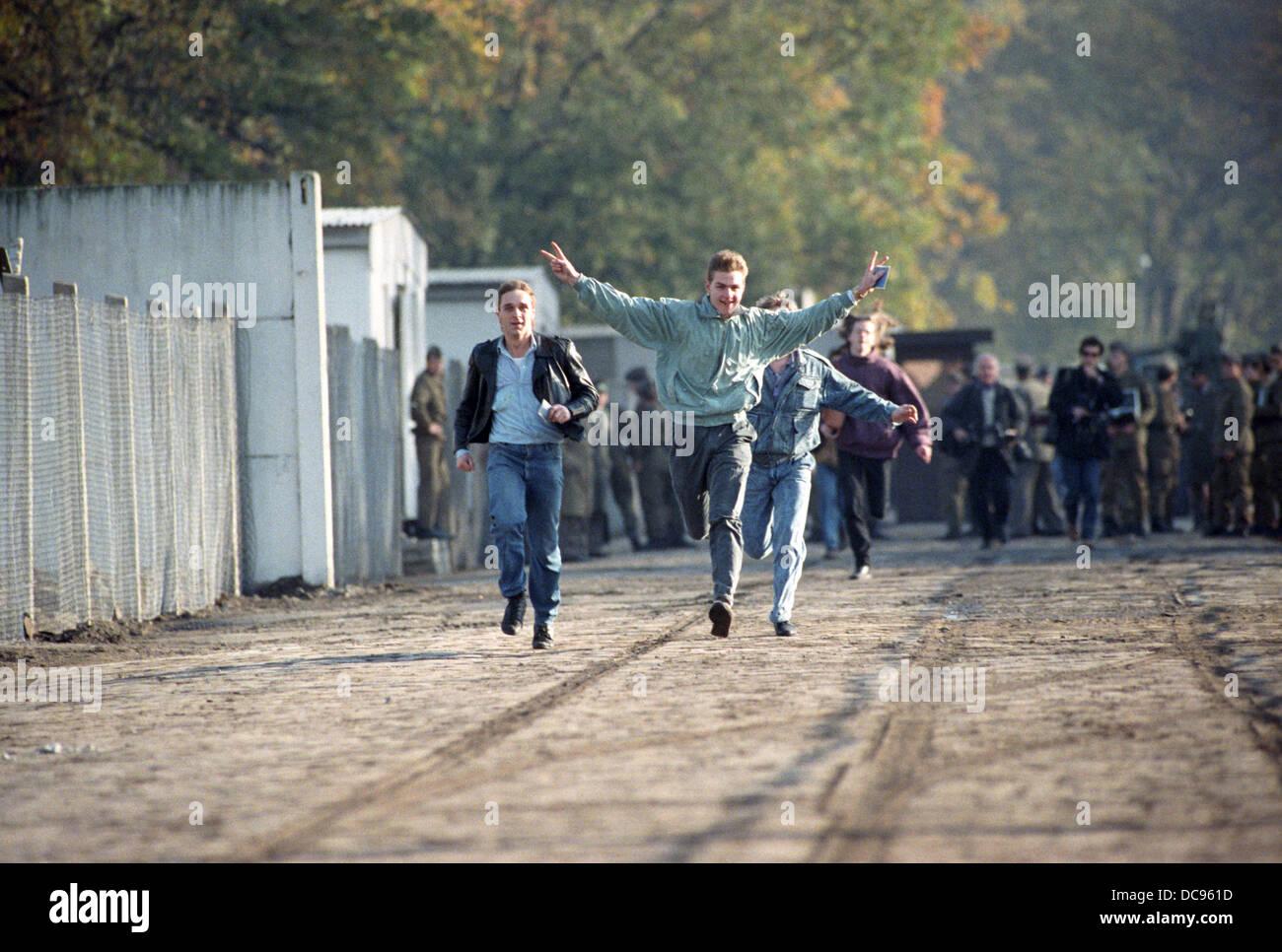 Junge Männer laufen jubeln über ein Broder Überfahrt Station in Berlin, Deutschland, 10 November Stockbild