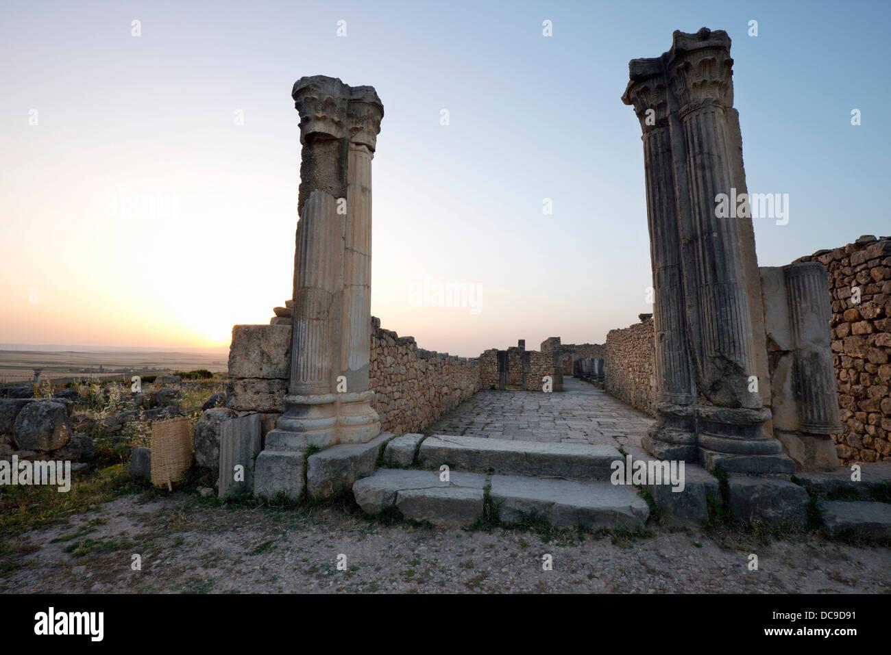 Antike römische Ruinen bei Sonnenuntergang an die teilweise ausgegrabenen römischen Stadt Volubilis in Stockbild