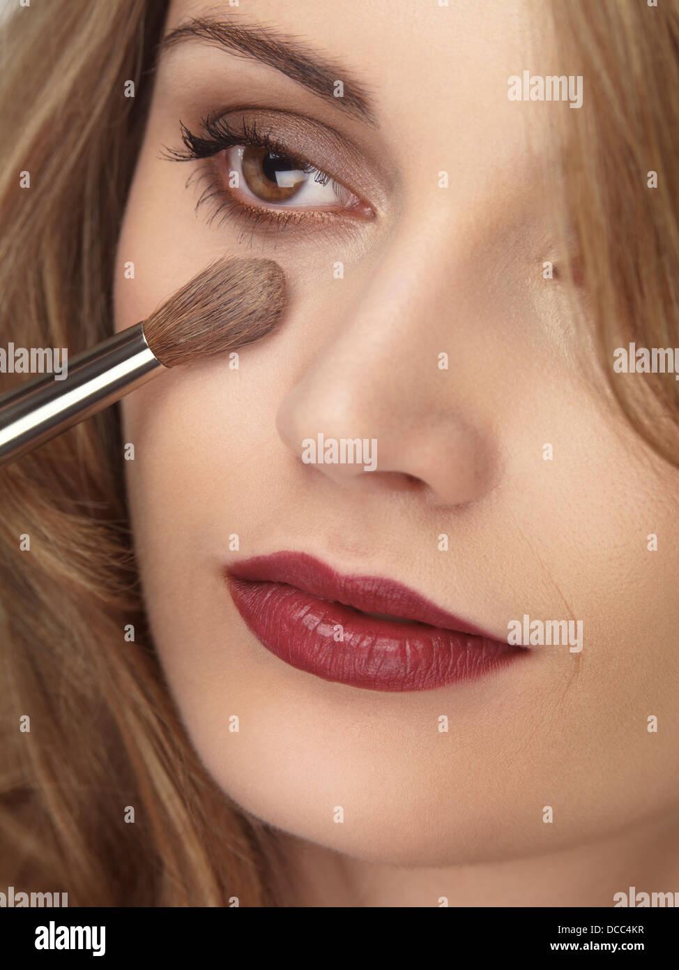 Nahaufnahme von einer jungen Frau Gesicht Foundation mit Make-up Pinsel auftragen Stockbild