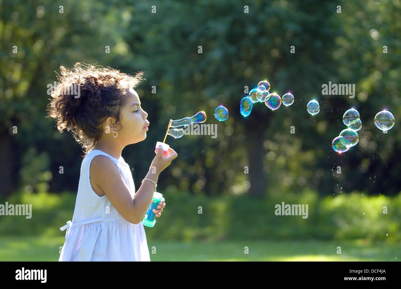 Kleines Mädchen bläst Seifenblasen im park Stockbild