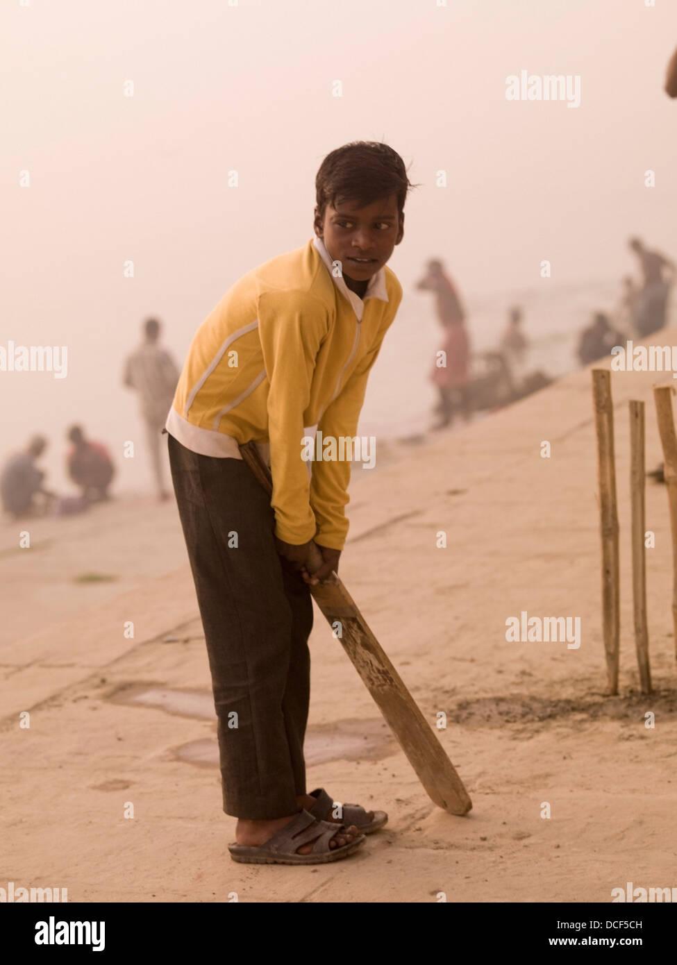 Kleiner Junge spielt Cricket von Ganges; Fluss Ganges, Varanasi, Indien Stockfoto