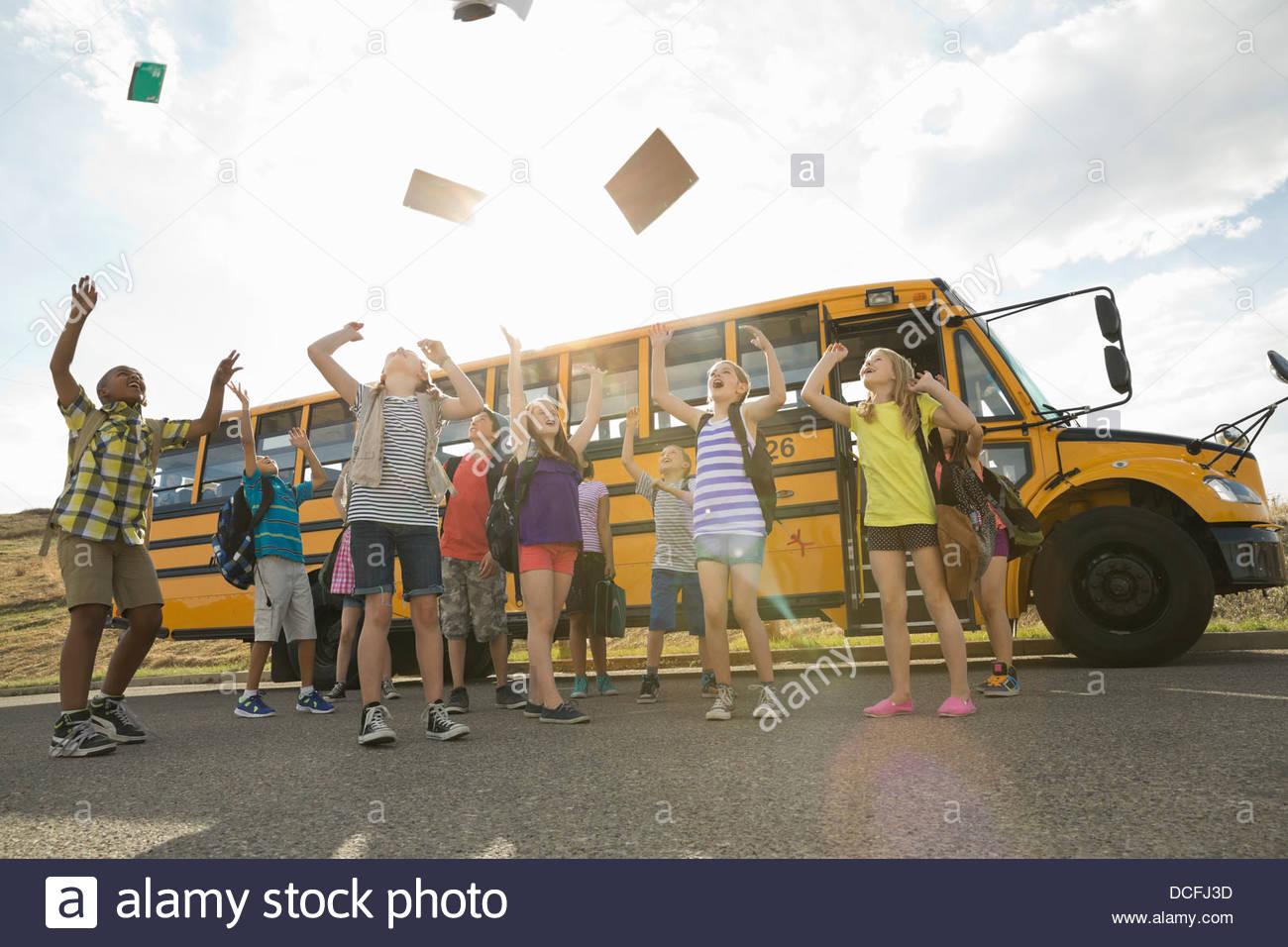 Aufgeregten Kinder kotzte Bücher in der Luft von Schulbus Stockbild