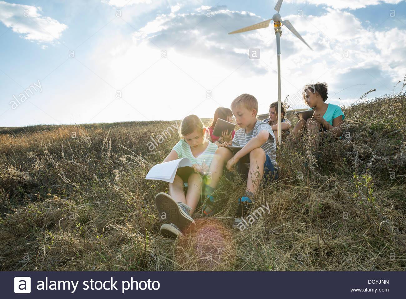 Schulkinder, die Notizen auf Wind-Turbine-Modell Stockbild