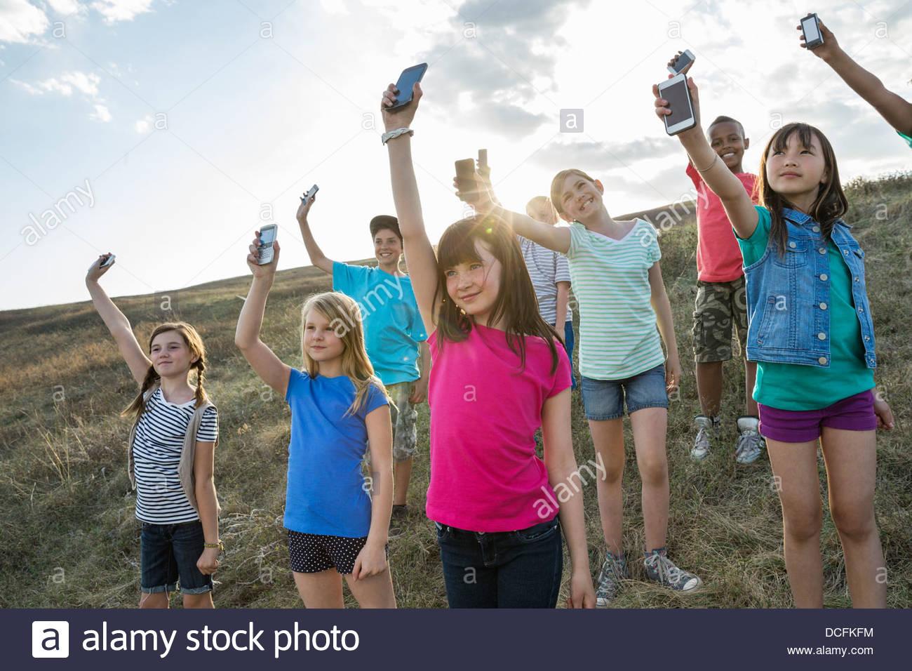 Gruppe von Kindern, die Mobiltelefone in der Luft halten Stockbild