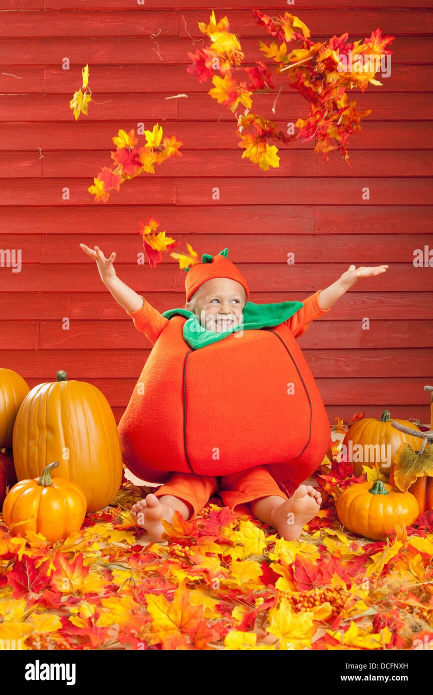 Ein Kind In Einem Kurbis Kostum Spielen Im Herbst Blatter Drei