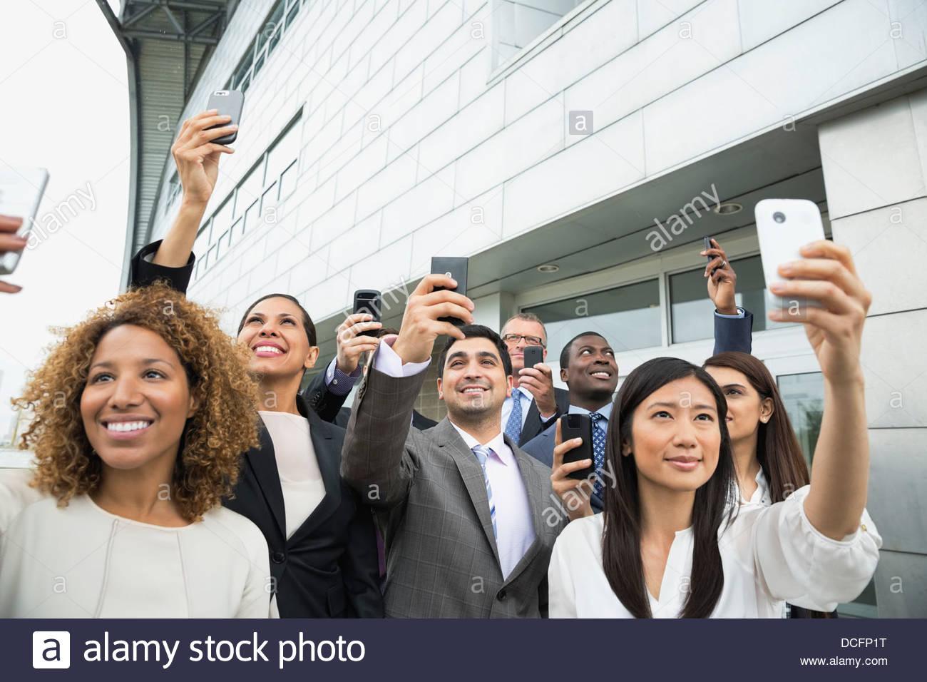 Gruppe von Geschäftsleuten, die Fotos mit Smartphones Stockbild