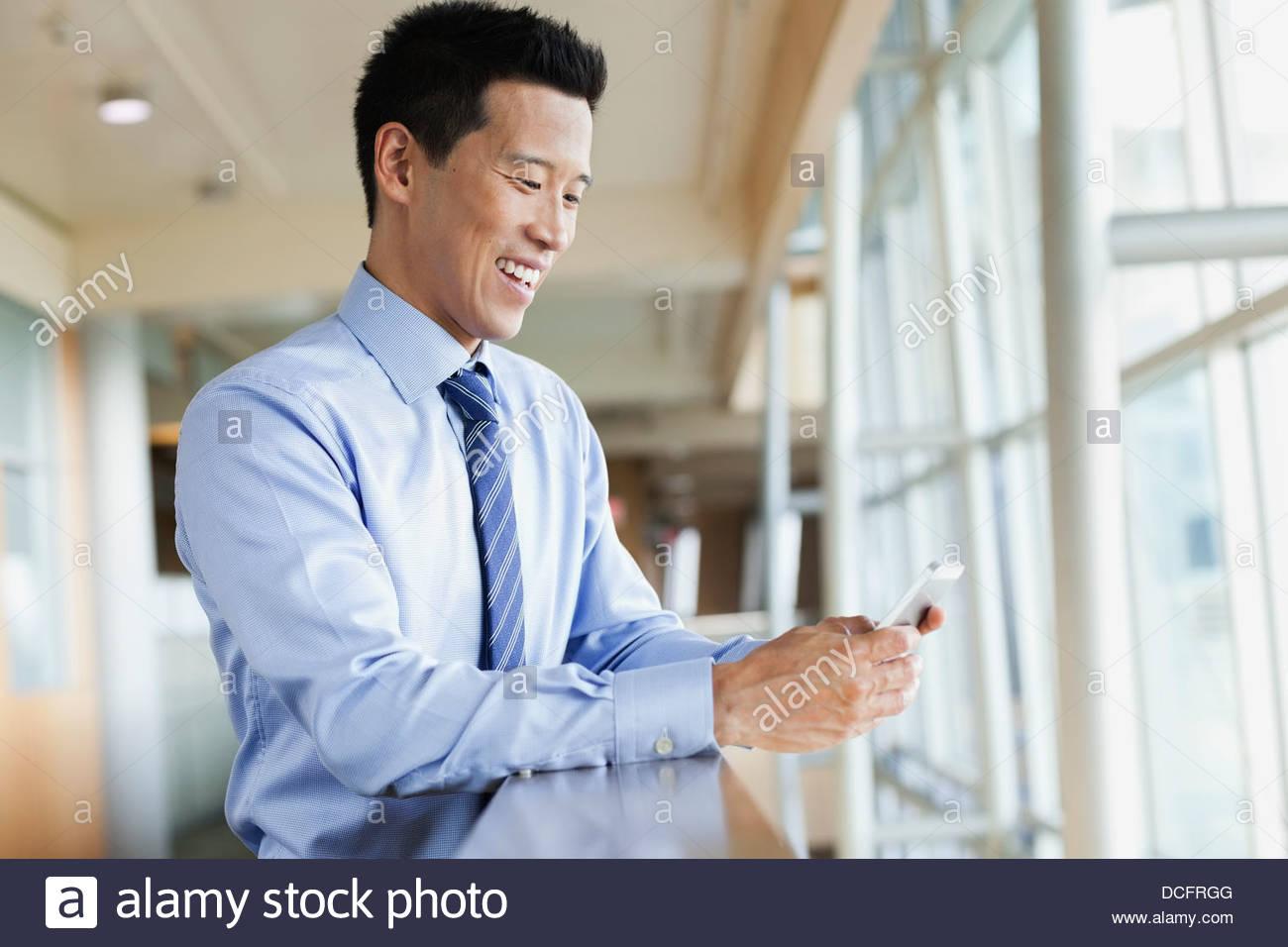 Lächelnde Geschäftsmann SMS lesen Stockbild