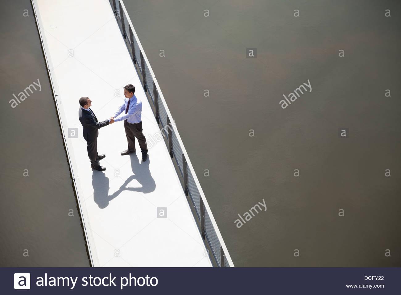 Erhöhte Ansicht der Geschäftsleute Händeschütteln auf Brücke Stockbild