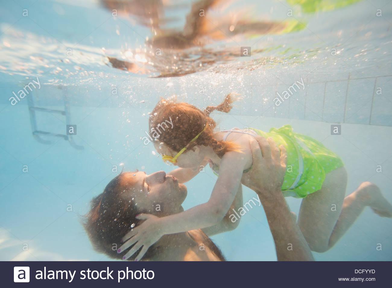 Vater und Tochter unter Wasser im Schwimmbad Stockbild