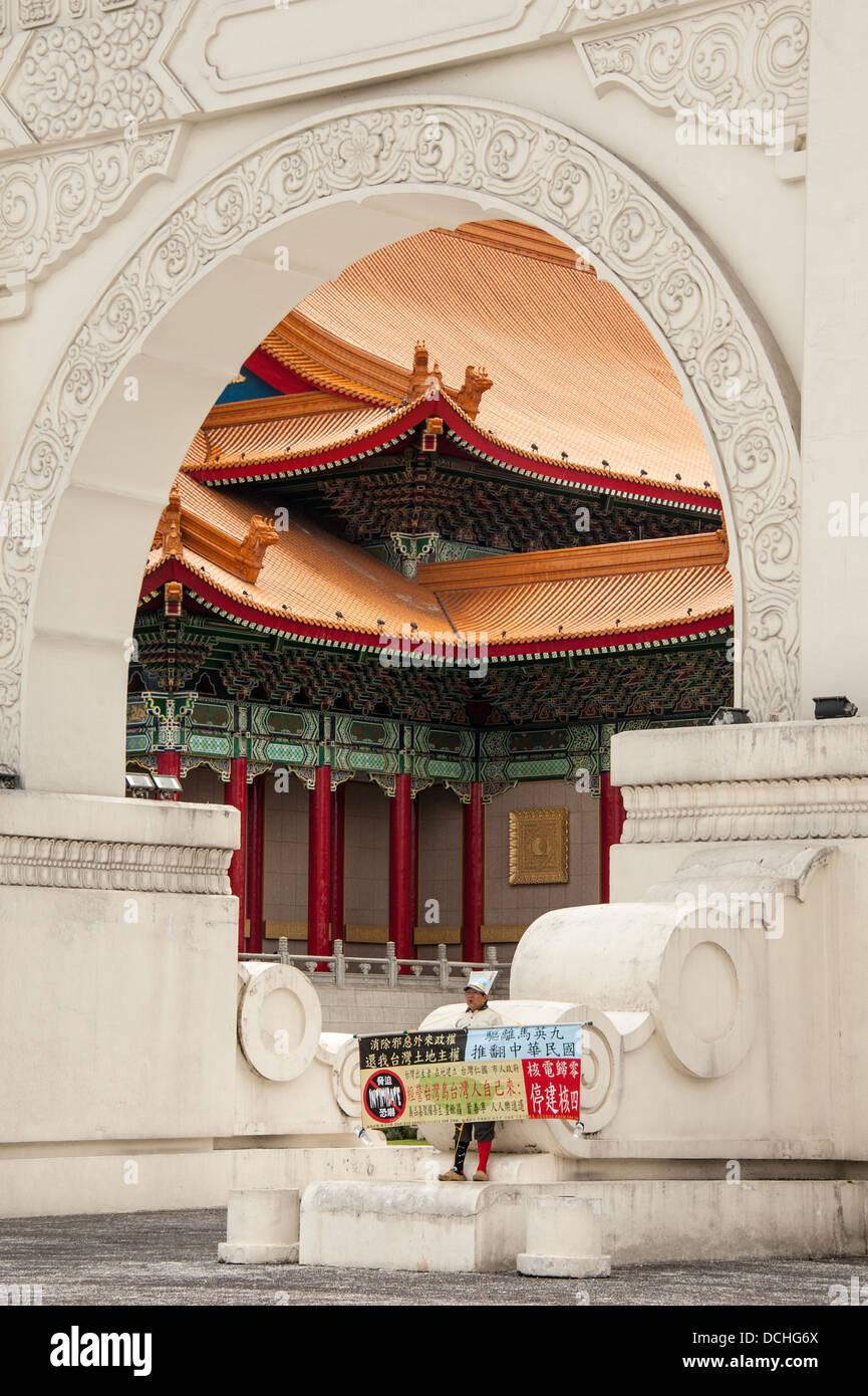 Ein einsamer Demonstrant zeigt einen Banner am Tor zum Memorial Hall Park in Taipei. Der National Concert Hall sieht Stockbild