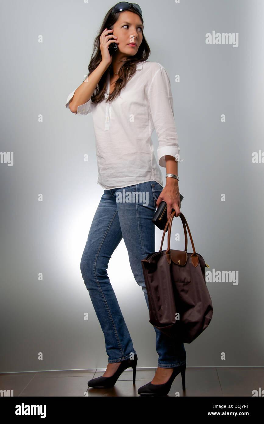 Frau auf das Geschäft mit Mobile und Tasche über die Schulter Stockbild