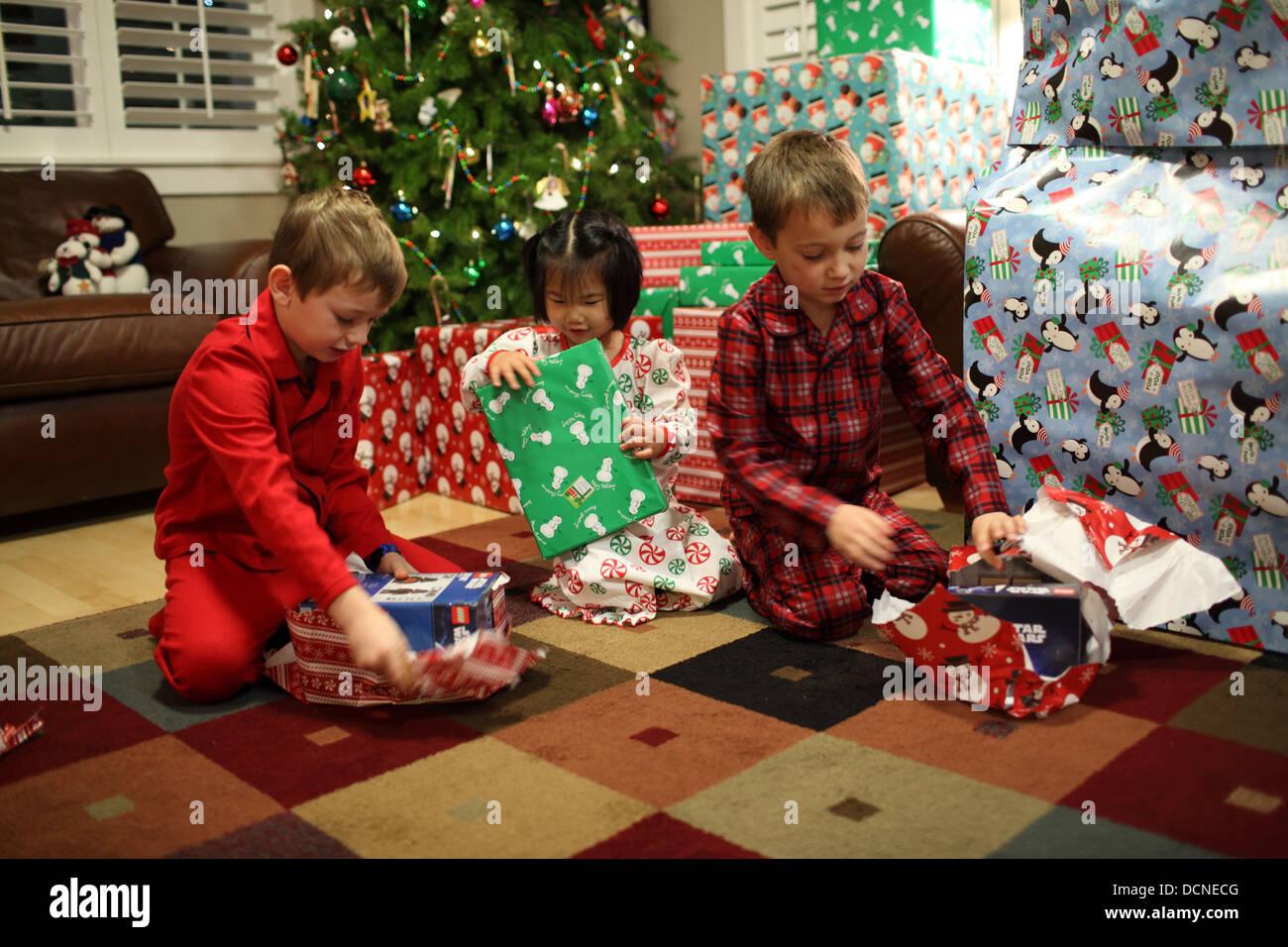 Drei Kinder Geschenke am ersten Weihnachtstag öffnen Stockfoto, Bild ...