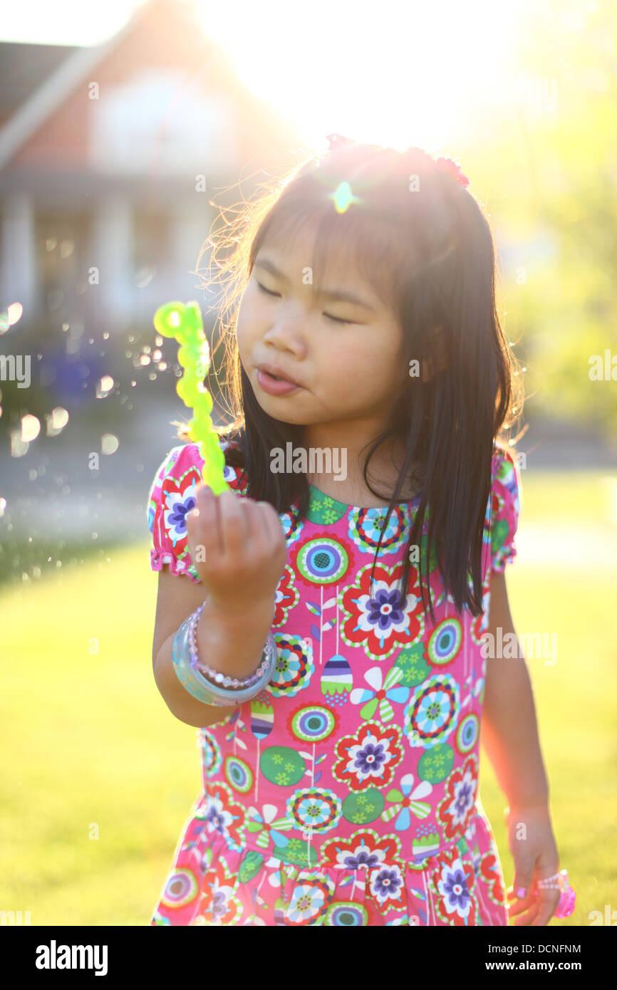Junges Mädchen bläst Seifenblasen im Freien im Sommer Stockbild