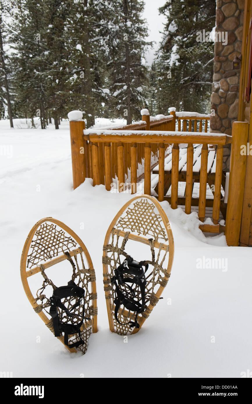 Traditionelle Schwimmhäuten Schneeschuhen im Schnee neben einem Blockhaus Patio; Lake Louise, Alberta, Kanada Stockbild